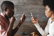 Internet Addiction Concept. Fashionable African Couple Using Mobile Phones Totally Absorbed In Online Life, Looking Obsessed, Not Talking To Each Other, Using Wi-fi At Cafeteria, Facing One Another