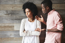 Young Displeased Black Male Gesturing In Indignation, Arguing With His Stylish Girlfriend, Who Is Standing Against Wooden Wall With Folded Arms, Looking Away With Offended Expression On Her Face