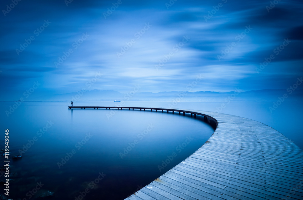 Fototapeta Young man looking to sea on curved jetty