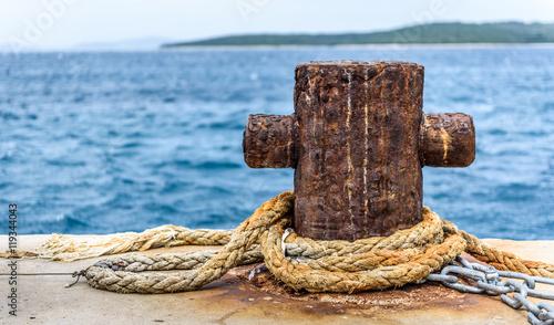 Fotografía  Old rusty steel mooring bollard pole on a pier.