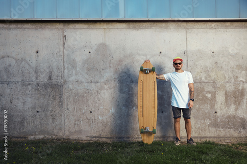 Photo  Serious looking surfer with beard, tattoos and sunglasses standing next to his l