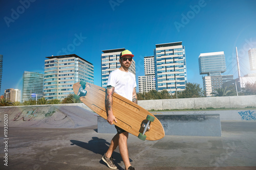 Photo  Surfer wearing a white blank t-shirt carrying a wooden longboard in a city skate