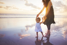 Mother Is Teaching Her Daughter Walks On The Beach