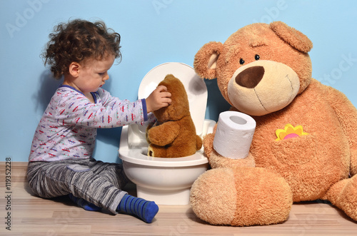 Baby toddler sitting on the floor teaching a small teddy bear who sits on a potty Wallpaper Mural