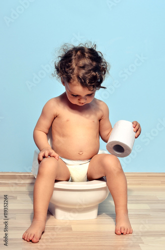 Photo Baby toddler sitting on the potty and playing with toilet paper