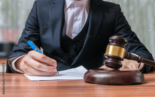 Fotografija  Lawyer is writing and gavel in front. Justice and Law concept.