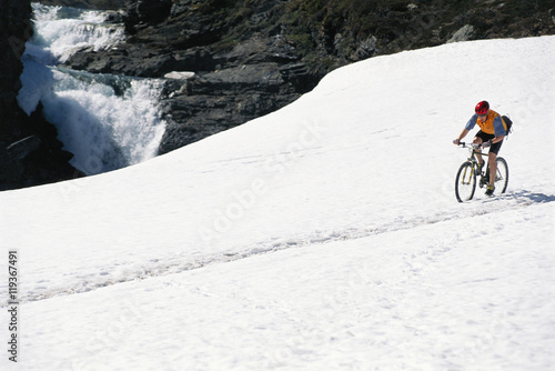 Fotobehang Wintersporten A man riding a bicycle in snow.