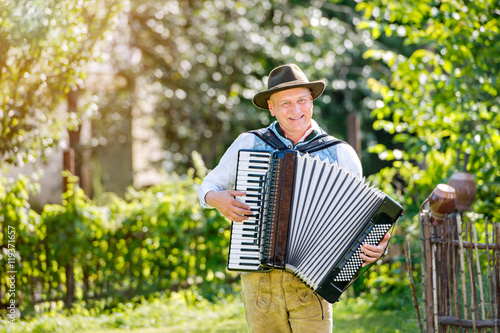 Photo Man in traditional bavarian clothes playing the accordion