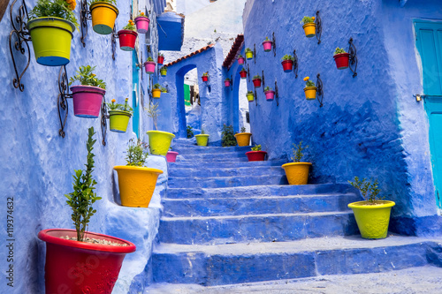 Fotobehang Marokko Morocco, Chefchaouen or Chaouen is most noted for its small narrow streets and neighborhoods painted in variety of vivid blue colors. Plantings in colorful pots line the narrow corridors.