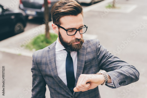 Businessman checking time while standing outdoors