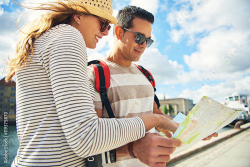 Young tourist couple looking at a map Canvas-taulu