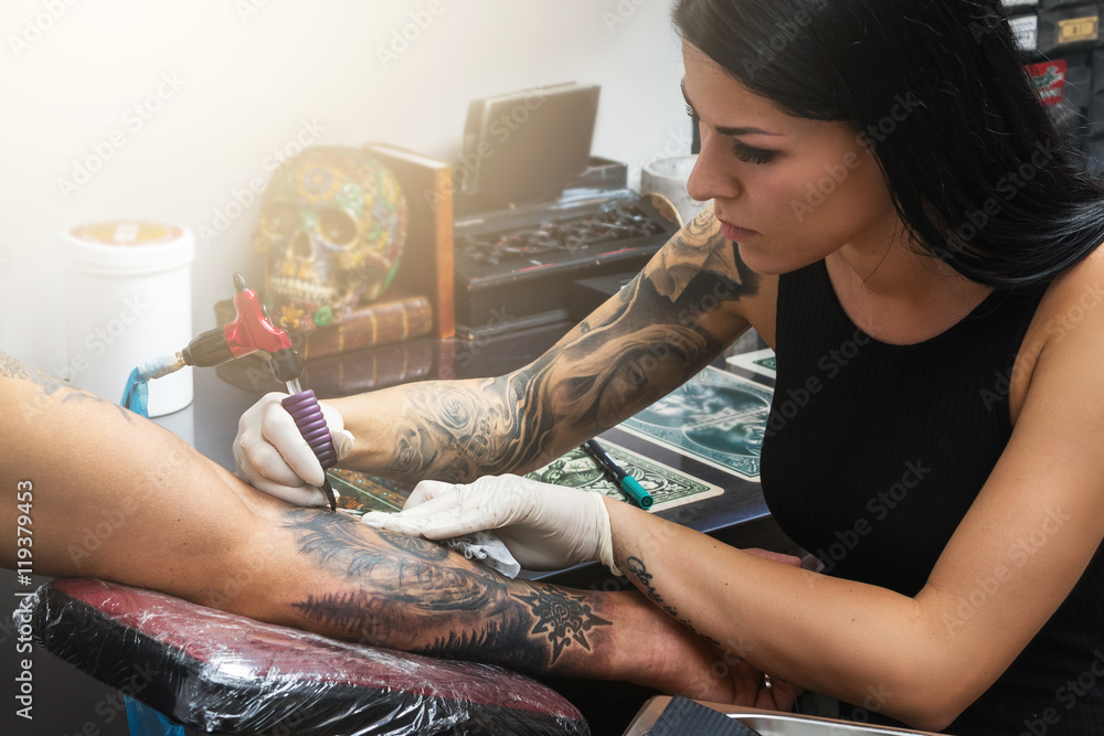 Fototapeta Tattoo artist during her work