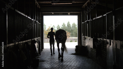 Young jockey is walking with a horse out of a stable. Man leadin