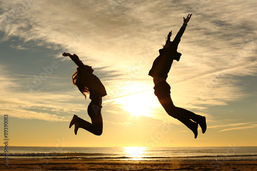 Fotografia  Couple or friends jumping on the beach at sunset