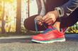 Female jogger tying her shoes outside