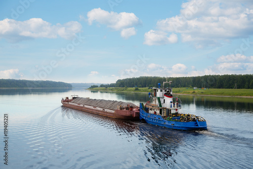 Tugboat moves barge on the Volga river Obraz na płótnie