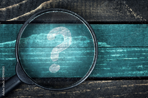 Fotografia  Question Mark painted and magnifying glass on table