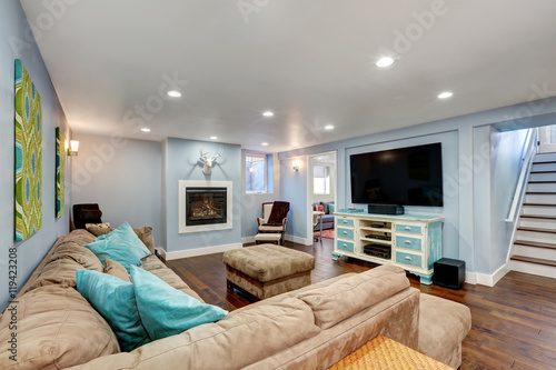 Photo Pastel blue walls in basement living room interior.