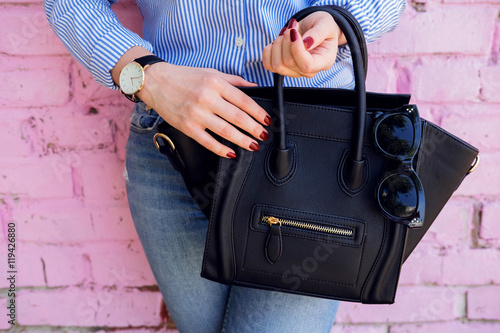 Photo  Close up black leather bag in hand of fashion woman.