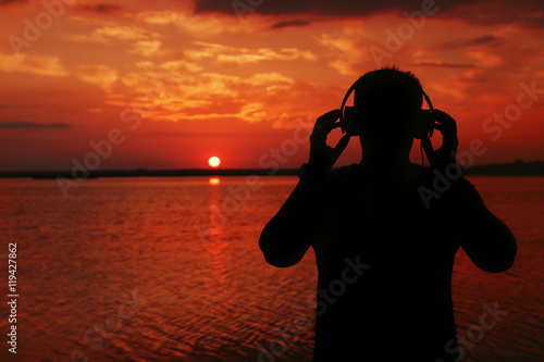 Ingelijste posters Rood traf. Silhouette of man with headphones on sunset sky background