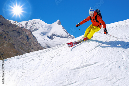 Tuinposter Wintersporten Skier skiing downhill in high mountains against sunshine