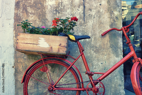 Türaufkleber Fahrrad Flowers on a red bicycle near the wall