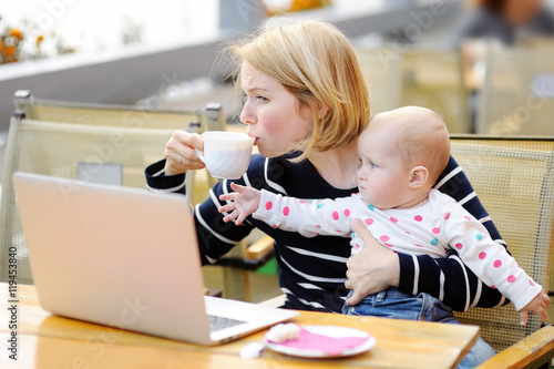 Foto  Tired young mother holding 6-month daughter and drinking coffee