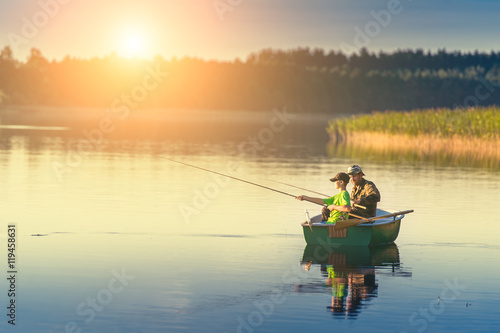 Foto father and son catch fish from a boat at sunset