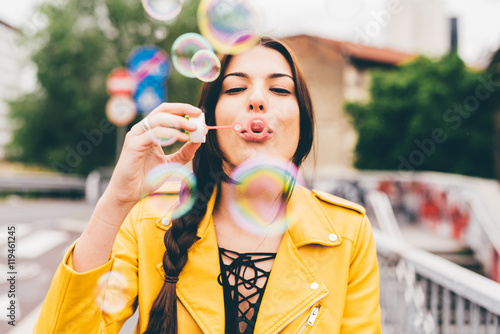 Fotografering  Portrait of young beautiful caucasian brown hair woman playing with bubblesoap -