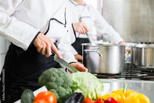 Fototapeta Team von Köchinnen beim Zubereiten von Gerichten in einer Kantinen-Küche obraz