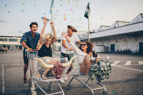 Fototapeta Young friends racing with shopping carts obraz