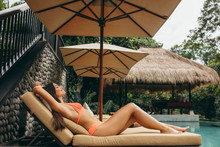 Happy Woman Lying On Deckchair At Poolside