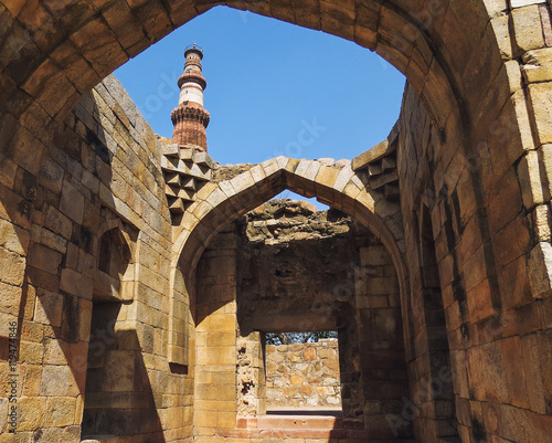 Foto op Aluminium Rudnes The ruins of the ancient monuments of Islamic architecture of XIII century Qutub Minar in Delhi, and the tower of the minaret looking out through them.