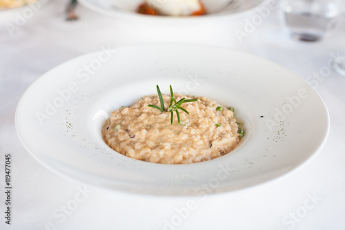 elegant circular bowl plate with rice in risotto and rosemary green leaf and chive pieces on white tablecloth in restaurant