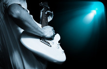 Musician Playing Electric Guitar On Stage With Spotlight