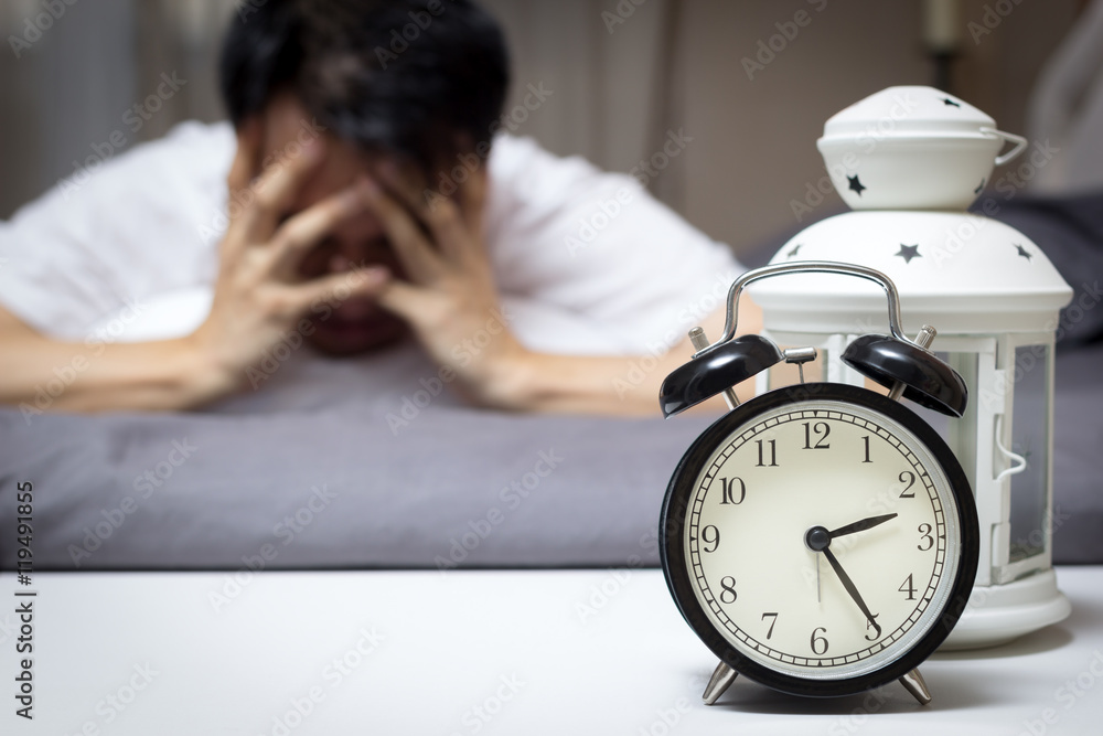Fototapeta asian man in bed suffering insomnia and sleep disorder thinking about his problem at night