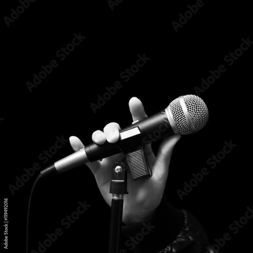 Photo singer right hand holding dynamic microphone, bw filter & isolated on black ( ha