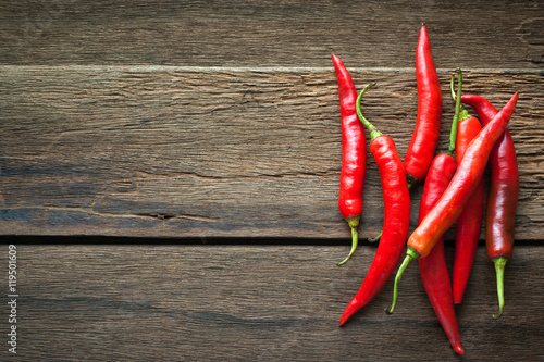 Poster Hot chili peppers red chili peppers on dark wooden background