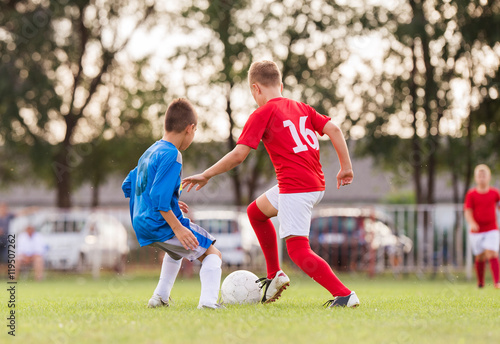 Boys playing football soccer game on sports field
