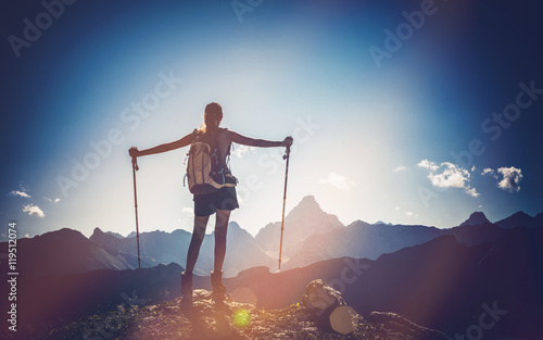 Female mountain climber stands triumphantly at top