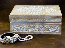 Old Carved Wood Jewellery Box And Pearl Necklace On Dark Background