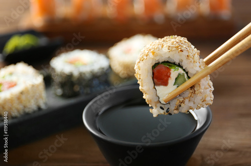 Foto op Aluminium Sushi bar Tasty sushi roll with wooden chopsticks and sauce in bowl