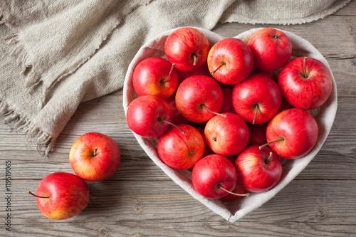 Plakat Czerwoni jabłka w koszykowym kierowym kształcie na drewnianym tle