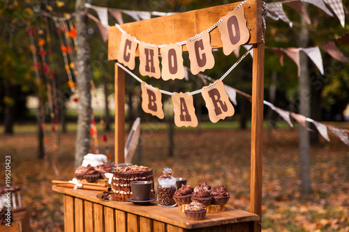 Spoed Foto op Canvas Chocolade Chocolate bar or stand in a vibrant autumn park
