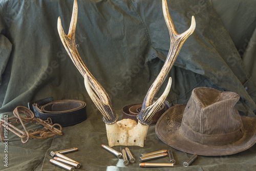 Foto op Aluminium Jacht Still life. Hunting rifle, antlers, some bullets, vintage trap,belt and cowboy hat on a wooden background in front of hunter clothes