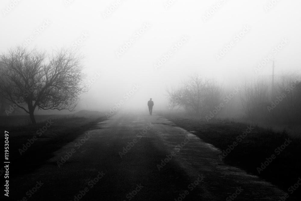 Fototapety, obrazy: Wayfarer in fog. Silhouette of man walking on misty village road. Homecoming. Loneliness, .nostalgia, sad mood. Black and white photo