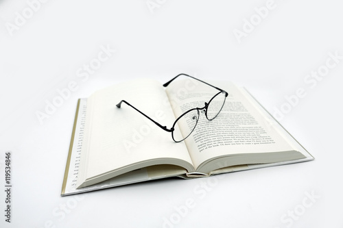 Fotografía  Reading Glasses with Open Book on White Background