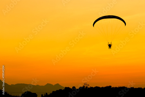 Deurstickers Luchtsport Glider, Paramotor flying with orange twilight sky