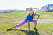 young happy woman doing stretching workout outdoors