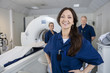 Leinwanddruck Bild - Female Radiologist With Colleagues Standing By MRI Machine